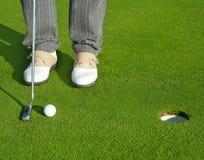 Golf al hombre verde del curso del agujero que pone la bola corta Fotos de archivo libres de regalías