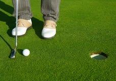 Golf al hombre verde del curso del agujero que pone la bola corta Imagen de archivo libre de regalías