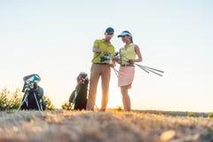 Golf al instructor que enseña una mujer joven a cómo utilizar a diversos clubs de golf foto de archivo libre de regalías