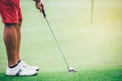 Golf al putter que pone a atletas para golpear una pelota de golf en el agujero a foto de archivo