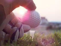 Golf auf dem wei?en T-St?ck auf dem gr?nen Rasen dort ist Sonnenschein lizenzfreies stockbild