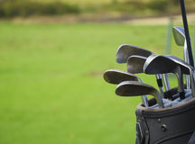 Golf bag with clabs. Golf bag with clubs after play on green grass background Stock Photos
