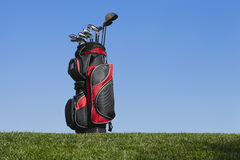 Golf bag and clubs against a blue sky. A red and black golf bag with clubs against a blue sky stock images