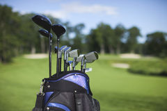 Golf bag and clubs against defocused golf course. A blue and black golf bag with clubs stands against a defocused golf course background royalty free stock photos