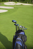 Golf bag and clubs against defocused golf course. A blue and black golf bag with clubs stands against a defocused golf course background royalty free stock image