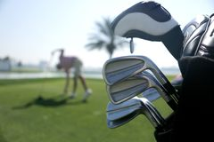 Golf bag with clubs on the plan and with the player before swing in the background stock photos