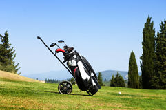 Golf bag on fairway. Golf bag with several clubs on a trolley on the fairway of a golf course royalty free stock photography