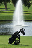 Golf Bag on the Golf Course. Golf bag sitting on the grass in front of a water fountain on a golf course royalty free stock photo