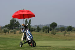 Golf bag on green with umbrella Royalty Free Stock Photos