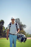 Golf bag man. Golf man walking with shoulder bag on course in fairway royalty free stock photography