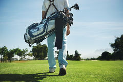 Golf bag man. Golf man walking with shoulder bag on course in fairway Royalty Free Stock Photos