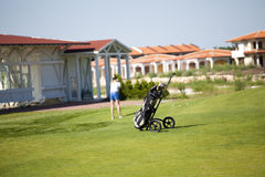 Golf bag with woman playing back. On a field Royalty Free Stock Photos