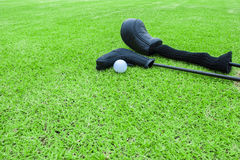 Golf bags and golf ball on a tee in green grass course Stock Image