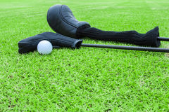 Golf bags and golf ball on a tee in green grass course Royalty Free Stock Photography