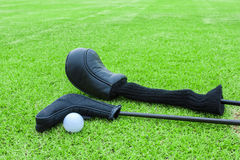 Golf bags and golf ball on a tee in green grass course Stock Images