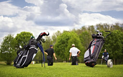 Golf bags with group of players. Two golf bags standing in front of a group of golf players putting on green Royalty Free Stock Photography