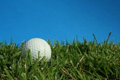 Golf ball. Lying in green grass with blue sky Stock Photo