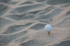 Golf ball. In the sand Royalty Free Stock Photos