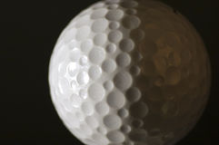Golf Ball. Isolated golf ball on black background. Highlights on left side Stock Images
