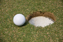 Golf Ball. Next to a golf ball in the hole Stock Images