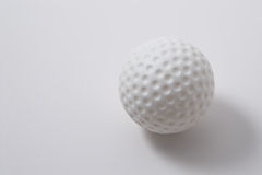 Golf ball. A white golf ball on a neutral background Royalty Free Stock Photo