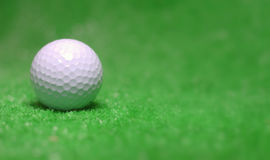 Golf Ball. A close up shot of a golf ball on a blurred green background Stock Photo