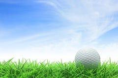 Golf ball. On green grass against blue sky stock image