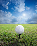 Golf ball. On a tee with grass and blue background Stock Photos