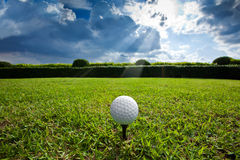 Golf ball. On a tee wait for golf playerwith grass and bluesky background Stock Photo