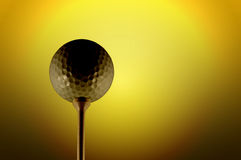 Golf ball. Picture of a golf ball on a tee with gold background Stock Image