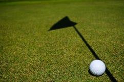 A golf ball. And the shadow of the hole flag Stock Photos