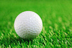 Golf ball. A golf ball against grass background Royalty Free Stock Images