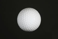 Golf Ball. Full shot of a golf ball isolated against a black background Royalty Free Stock Image