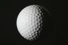 Golf Ball. Half lit from left, isolated on a black background Royalty Free Stock Images