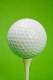 Golf ball. Close up of golf ball on tee against green background Stock Images