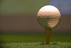 Golf ball. On stick and artificial grass surface Royalty Free Stock Photo