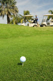 Golf ball against golf carts. White Golf ball against golf carts Stock Photos