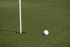 A golf ball approaches the hole on the green Stock Images