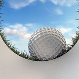Golf ball approaching hole Stock Images