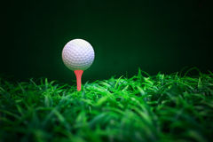 Golf ball ball driver and tee on green grass field. File of golf ball on red tee and green grass field Stock Photography