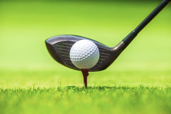 Golf ball behind driver at driving range Stock Photo
