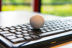 Golf ball with black computer keyboard Royalty Free Stock Photos