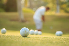 Golf ball and blurred of man playing golf in green course stock image