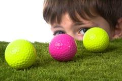 Golf ball boy. Boy peaking around a golf ball Royalty Free Stock Photography