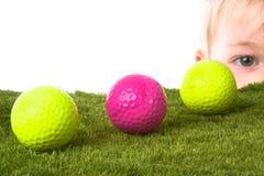 Golf ball boy. Boy peaking around a golf ball Royalty Free Stock Photo