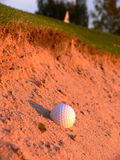 Golf Ball in Bunker. A golf ball in the green bunker close to the flag Stock Photos