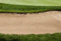 Golf ball on a bunker sand trap hazard in a golf course. Royalty Free Stock Image