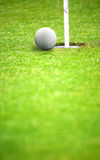 Golf ball close to hole Stock Images