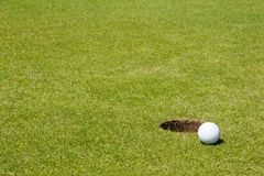 Golf ball close to a hole. Golf ball very close to a hole on a putting green. Deep depth of field Royalty Free Stock Images