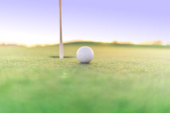 Golf ball close to hole on green Stock Photo